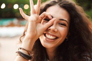 Jonge vrouw krullen blij tanden bloot lachen geeft teken oke okay alles goed mooie lach